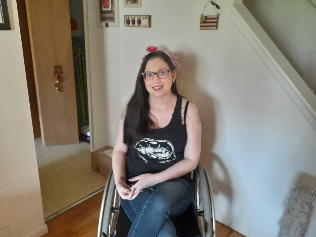 A white, nonbinary femme with long black hair and glasses sits in a wheelchair, smiling. They are wearing a black tank top with screen printed image of a mouth with fangs. Their legs are crossed.
