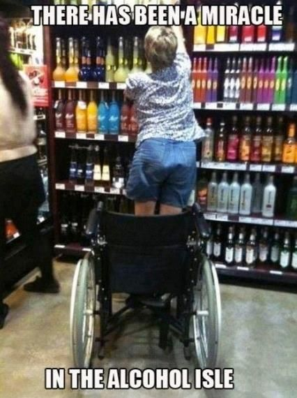 """A photo taken of a person in jean shorts and a blue t-shirt standing up from their wheelchair to reach a bottle of liquor from shelves filled with many kinds of alcoholic beverages. The text on the photo, which makes it a meme, reads, """"There has been a miracle in the alcohol isle"""" (sic)."""